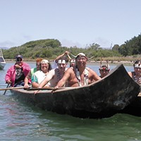 Tribal members in dugout canoes make their way from Indian Island to the Adorni Center for a ceremony marking the return of part of the island to the Wiyots in 2004.