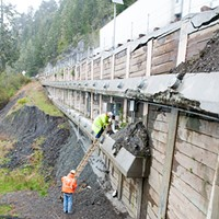 Workers gather data from load sensors on a retaining wall at one of the fail points.