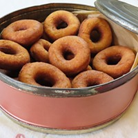 Ma's tin filled with doughnuts made from her recipe with her old kettle.