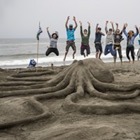 "The Northcoast Environmental Center team members took to the air when they finished their ""Lend a Hand, or Eight"" sand sculpture. It later won the People's Choice award."