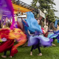 A slow shutter speed allowed the colorful costumes of the belly dancing group Ya Habibi in front the Enchantment Stage to blur in the photo.