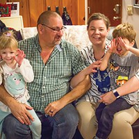 George and Tiffany Strango holding their adopted children, Ellie and Joey. Even after adopting, the Strangos continue to keep their doors open for foster children.