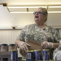 Food bank volunteer Emogene Thomas, 68, arranges cans on a table at Teamsters 315 Hall in Martinez on March 19, 2020. The food bank serves seniors but had about half regular the number of visitors due to coronavirus concerns.