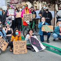 """Protesters record law enforcement and demonstrators chanting, """"No justice, no peace, no racist police"""" on June 1."""