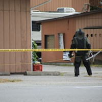 Humboldt County Sheriff's deputy wearing safety gear to examine the package.