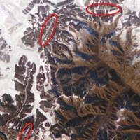 Enlargement of part of a digital photo of Inner Mongolia about 200 miles north of Beijing, taken with a 180 millimeter telephoto lens from the International Space Station in November of 2004. Thanks to fresh snow and bright sunlight, sections of the Great Wall of China can be seen (in red ovals). No astronaut has reported seeing the wall with the naked eye.