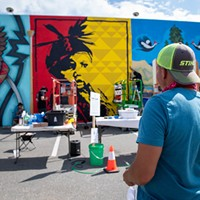 """Alme Allen looks at his nearly completed mural """"Arareethívthaaneen"""" on the back wall of the Discovery Shop on the last day of the festival."""