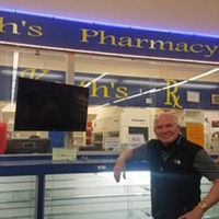 Keith Lorang poses in front of empty shelves at his pharmacy which is closing at the end of Friday.