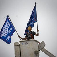 A masked parade participant waves campaign flags from a crane bucket above a truck parked at the end of the caravan in McKinleyville.