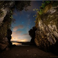 The cave's mouth opened onto a world of dazzling light and color beneath the cosmos. A shooting star stabbed across the camera's eye. The bright point near its tip is Saturn, while the brightest point is Jupiter. To their right is the Milky Way. Sept. 18, 2020. Moonstone Beach, Humboldt County, California.