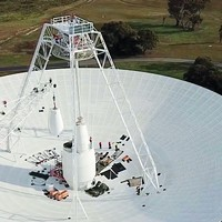 A crane moves one of the white feed cones that house part of the antenna's receivers during the recent seven-month upgrade of the 70-meter Deep Space Station 43 located near Canberra, Australia.