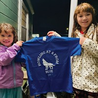 Shelby (left) and Alexis Wickizer display a t-shirt somebody dropped off at their house in appreciation of their persistent nightly howling.
