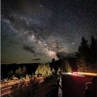 With the grand Milky Way soaring overhead, streaking car lights in the southbound lanes of U.S. Highway 101, paralleling the Eel River valley, converge with the brighter streaks of a car leaving the Vista Point south of Stafford, Humboldt County. June 9, 2021.