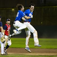 Crabs third baseman David Morgan (No. 20) leaps into the air and hugs teammate Andrew Allanson (No. 22) as he jumps up after hitting the walk-off base hit to win the game against the Redding Tigers in the bottom of the 11th inning on July 20, 2021.