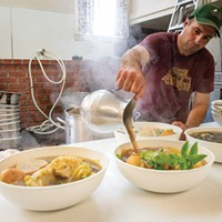 Kevin Oliveira pours the sopas do Espírito Santo broth over the bread and mint.