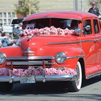 A flower festooned Ford rolls through town.