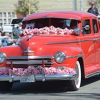 A flower festooned Ford rolls through town.