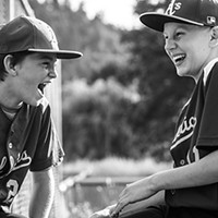 """First Place Winner: John Harding, left, and Enzi Stuggard share a laugh with their team at the plate during a May 30 baseball game in Redway. """"I was taking action photos and then turned around and snapped this because friendships made, both with the kids playing and their parents, are such a big part of sports,"""" explains photographer Briar Parkinson. """"These boys go to different schools but are friends through the sports community."""""""