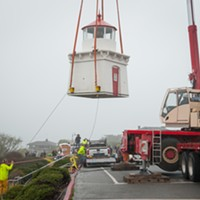 Two workers tie ropes to align the lighthouse as it is moved to a trailer.