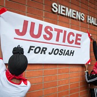 "Students hang a ""Justice for Josiah"" banner on the Humboldt State University quad earlier this month. A similar banner hung outside the D Street Neighborhood Center for the Community Dialogue on Race."