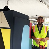 Jonathan DeSoto painting a utility box on the corner of E and Fourth streets in Eureka.