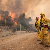 Chris Mitchell, left, and Arly Allen watch the progress of the fire as it slowly burns towards a private road on the Cache Creek Winery in Lake County.