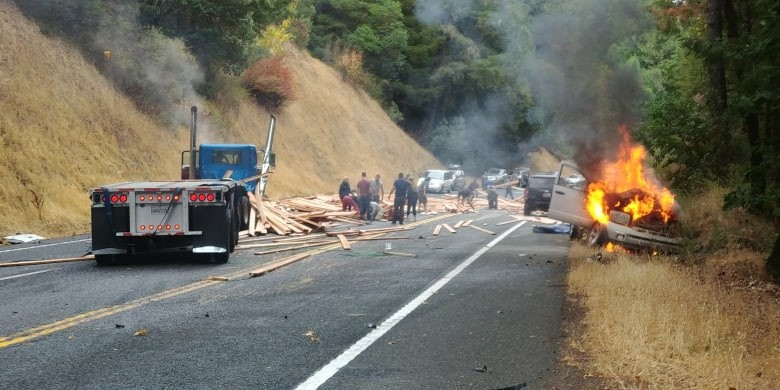 A vehicle burns as onlookers attempt to remove lumber from the road. - PHOTO COURTESY OF  CHRIS BRANNAN