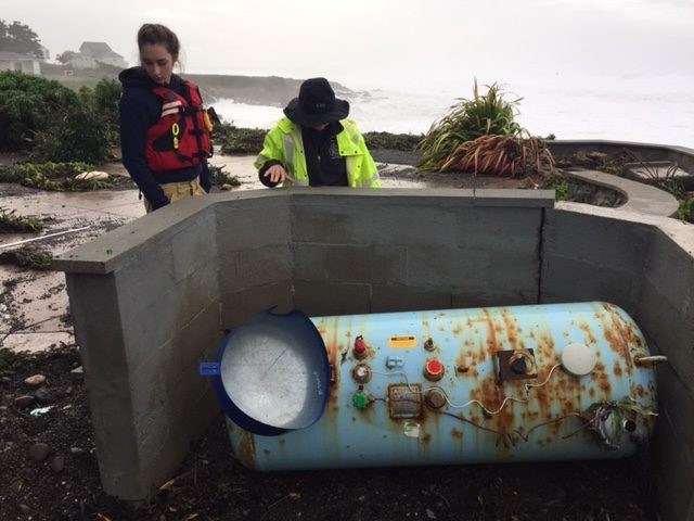 Shelter Cove Fire Crew members, wearing life vests, examine this propane tank  which was shoved off its mountings. - CHERYL ANTONY OF SHELTER COVE FIRE
