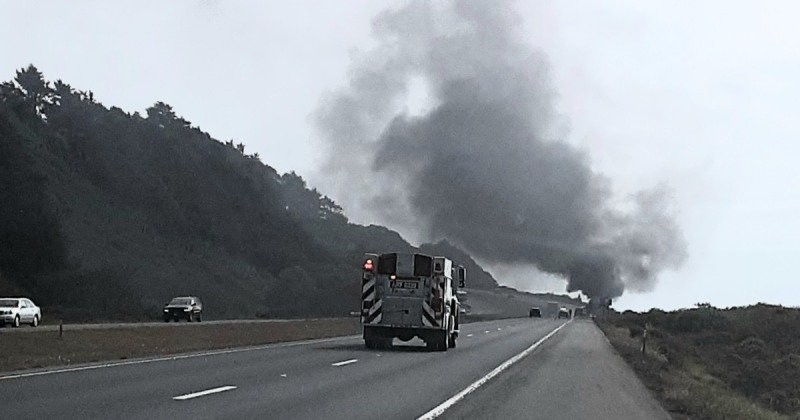 A fire truck rushes to the scene as smoke rises from a fully engulfed vehicle on 101. [Photo from Mary Ann Machi]