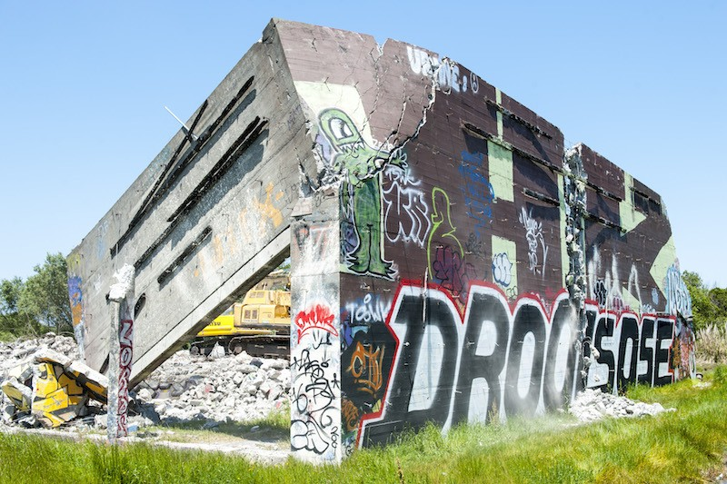 The lone remaining wall of the Devil's Playground teeters as a crew works to demolish it Thursday. - MARK MCKENNA