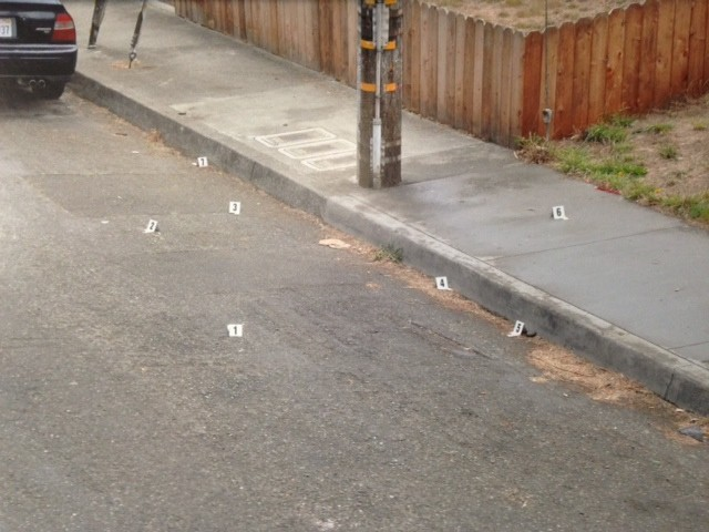 A police photo of the scene of the fatal shooting. Numbered white evidence markers show the locations of where California Department of Justice investigators found seven shell casings from officer Steven Linfoot's gun. - THADEUS GREENSON