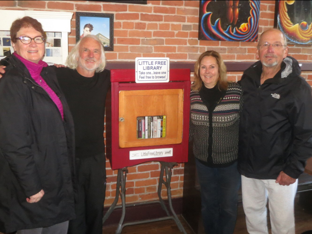 The Little Free Library in Old Town Coffee and Chocolates, started by Journal contributors Barry Evans and Louisa Rogers. From left to right: Rebecca Kalal, Barry Evans, Gail Mentink and Gil Yule. - SUBMITTED