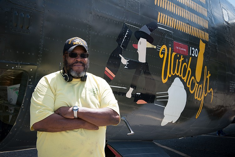 "Chef ""Grizzly"" Adams stands by the 130 bombs painted on the side of the Witchcraft — one for every successful mission. - PHOTO BY MARK MCKENNA"