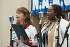 Donna Landry-Rehling (left) and Elizabeth Smith sing during the celebration of the life and legacy of Dr. Martin Luther King, Jr. at the Adorni Center on Monday.