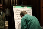 """An attendee signs onto the pledge stating """"I believe in the dignity of all people and I will work to ensure that everyone in Eureka has a safe place to call home."""""""