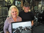 Jerry and Betty Brazil in front of their dragster and holding a photo of three generations of Brazil racers.