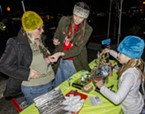 Mindy Hiley, director of SCRAP Humboldt, demonstrated how to make an ugly sweater on volunteer Patti Johnson with help from Leda at a workshop table during the Wonder and Light event on the Arcata Plaza on Friday, Dec. 2. An Ungly Sweater Walk/Run was scheduled for Sunday, Dec. 4.