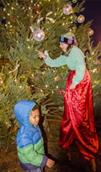 "Holiday elf Frida King (on stilts), of Blue Lake, help place a ""wish"" ornament created by Jahme Wester, of Arcata, in a tree-lighting ceremony."