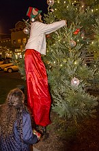 "Holiday elf Bella Fratkin (on stilts), of Kneeland, placed Kehlan Wester's ""wish"" ornament on the tree."