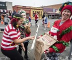 "Kualli Major, of Arcata, has to pause and think about where to place her name on the ""naughty"" or ""nice"" list worn by Beth Erquhart, of McKinleyville."
