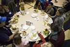 A table full of people enjoying a meal prepared by volunteers and staff from Arcata Elementary at the Bowl of Beans Benefit on Monday, Jan. 16.