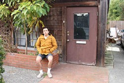 PHOTO BY SKYE KIMYA - Oliver Winfield-Perez sits in front of his old home, which had a rat problem so bad he and his roomates started counting how many they killed and got up to 20.