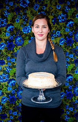 AMY KUMLER - Owner Sue Charnes holding a vegan carrot cake.