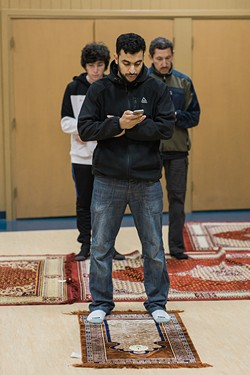 PHOTO BY LEÓN VILLAGÓMEZ - Alaa Abdelrahman reads a prayer from the Quran on his phone as Nabil and Emran Essa pray behind him.