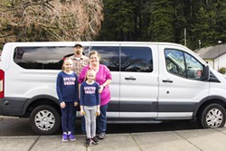 PHOTO BY T.WILLIAM WALLIN - Scott and Heather Peugh with their daughters Ariel (left) and Aurora. The Peughs invested in this 12-seat van because they needed to accommodate the amount of children they foster.