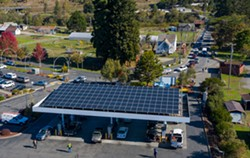 MARK MCKENNA - A line of cars waiting to fuel up stretches down the block at the Blue Lake Rancheria gas station, which used microgrid technology, including the solar panels above the pumps, to keep operating through the blackout.