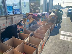 PHOTO COURTESY OF THAVISAK SYPHANTHONG - Left to Right: Ampha Mannorind, Amalah Syphanthong, Bao Syphanthong, Pata Vang, Onetha Sayavong and Yuhmong Lo pack boxes with food, school supplies and first aid kits, as well as information about COVID-19 and the shelter-in-place order translated into Hmong and Lao.