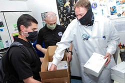 COURTESY OF HUMBOLDT COUNTY EMERGENCY OPERATIONS CENTER - Humboldt County Public Health Laboratory Manager Jeremy Corrigan (right) inspects testing reagents recently delivered by the California National Guard 59th Civil Support Team in Hayward.
