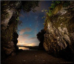 PHOTO BY DAVID WILSON - The cave's mouth opened onto a world of dazzling light and color beneath the cosmos. A shooting star stabbed across the camera's eye. The bright point near its tip is Saturn, while the brightest point is Jupiter. To their right is the Milky Way. Sept. 18, 2020. Moonstone Beach, Humboldt County, California.