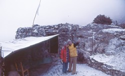 COURTESY OF LOUISA ROGERS - Louisa Rogers and her husband, Barry Evans, in the Himalayas, outside the teahouse hut where they stayed below Thorong La.